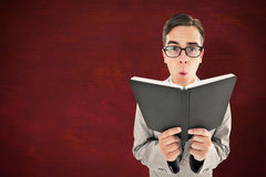 Composite image of geeky preacher reading from black bible Stock Photos