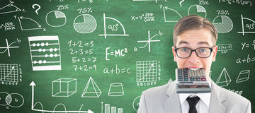 Composite image of geeky smiling businessman biting calculator Royalty Free Stock Image