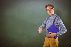 Composite image of geeky student holding a notebook. Geeky student holding a notebook against green chalkboard Stock Image