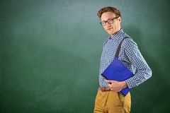 Composite image of geeky student holding a notebook. Geeky student holding a notebook against green chalkboard Royalty Free Stock Images