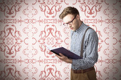 Composite image of geeky student reading a book Stock Photos