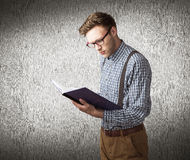Composite image of geeky student reading a book Royalty Free Stock Photo