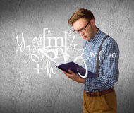 Composite image of geeky student reading a book Stock Images