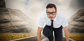 Composite image of geeky young businessman ready to race Stock Image
