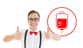 Composite image of geeky young hipster showing thumbs up. Geeky young hipster showing thumbs up against blood donation Stock Photos