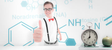 Composite image of geeky young hipster showing thumbs up. Geeky young hipster showing thumbs up against desk Stock Photo
