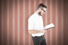 Composite image of geeky young man reading from black book. Geeky young man reading from black book against background Royalty Free Stock Photo