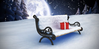 Composite image of gift box on park bench Stock Photos
