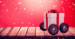 Composite image of gift box with red ribbon on wheels Royalty Free Stock Image