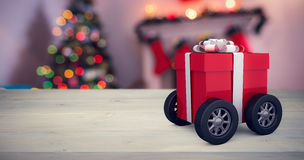 Composite image of gift box wrapped in red paper with ribbon on wheels. Gift box wrapped in red paper with ribbon on wheels against defocused of christmas tree Royalty Free Stock Image