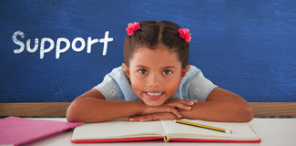 Composite image of girl clenching teeth while leaning on book Royalty Free Stock Photo