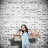 Composite image of girl with fake wings pretending to be pilot. Girl with fake wings pretending to be pilot against grey brick wall Stock Photo