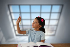 Composite image of girl looking at pencil while sitting at desk Royalty Free Stock Images
