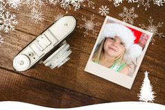 Composite image of girl wearing santa hat at home. Girl wearing Santa hat at home against view of an old camera Royalty Free Stock Photography