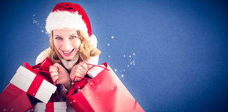 Composite image of girl in winter fashion holding presents and shopping bags Royalty Free Stock Photos