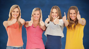 Composite image of girls sticking their thumbs up Stock Images