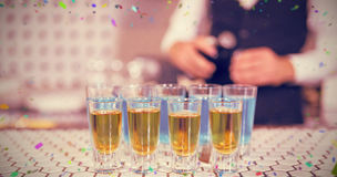 Composite image of glass of blue lagoon drinks and whisky on bar counter Royalty Free Stock Photography