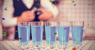 Composite image of glasses of blue lagoon drinks on bar counter Royalty Free Stock Photos