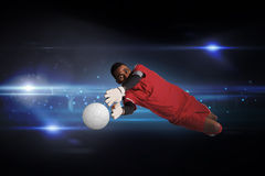 Composite image of goalkeeper in red making a save Stock Photos