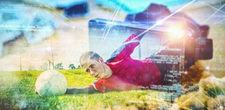 Composite image of goalkeeper in red making a save. Goalkeeper in red making a save against virtual reality headset on desk royalty free stock photography