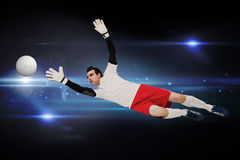 Composite image of goalkeeper in white making a save. Goalkeeper in white making a save against black background with spark royalty free stock image