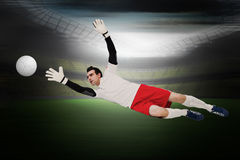 Composite image of goalkeeper in white making a save Royalty Free Stock Photography