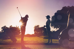 Composite image of golfing couple playing together stock photos