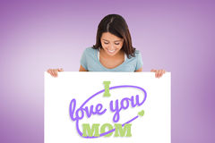 Composite image of good looking woman holding a  board. Good looking woman holding a  board against purple vignette Stock Images