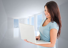 Composite image of good looking woman relaxing with her laptop Stock Photography