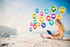 Composite image of gorgeous blonde in bikini using laptop on the beach Stock Photography