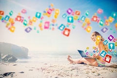 Composite image of gorgeous blonde in bikini using laptop on the beach Stock Photo