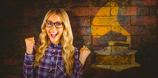 Composite image of gorgeous blonde hipster celebrating success Stock Photos