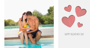Composite image of gorgeous couple sitting poolside on holidays Royalty Free Stock Photo
