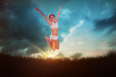 Composite image of gorgeous fit blonde jumping with arms out Stock Images