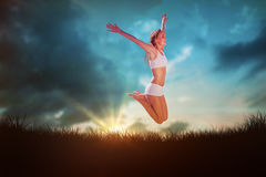 Composite image of gorgeous fit blonde jumping with arms out Stock Photography