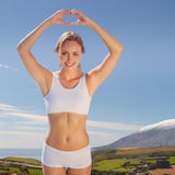 Composite image of gorgeous fit blonde making heart shape with hands by the sea Stock Photo