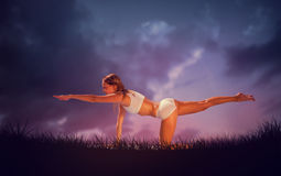 Composite image of gorgeous fit blonde in pilates pose on the beach. Gorgeous fit blonde in pilates pose on the beach against blue sky over grass Stock Photos