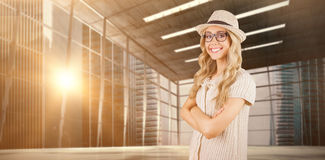 Composite image of gorgeous smiling blonde hipster with arms crossed Stock Photos