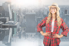 Composite image of gorgeous smiling blonde hipster with hands on hips Stock Photography