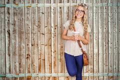 Composite image of gorgeous smiling blonde hipster leaning against red brick background Stock Photography