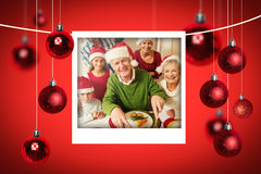 Composite image of grandfather in santa hat carving chicken at christmas dinner Royalty Free Stock Images