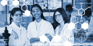 Composite image of graphic image of chemical structure. Graphic image of chemical structure against portrait of schoolgirls doing a chemical experiment in Stock Image