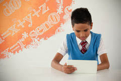 Composite image of graphic image of equations. Graphic image of equations against schoolboy using digital tablet Stock Photo