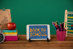 Composite image of graphic image of red back to school text. Graphic image of red back to school text against school supplies with digital tablet on wooden table royalty free stock photo