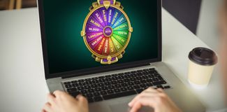 Composite image of graphic image of wheel of fortune on mobile screen. Graphic image of wheel of fortune on mobile screen against cropped hands of woman using Royalty Free Stock Images
