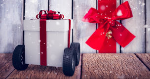 Composite image of gray gift box with wheels Stock Photo