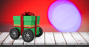 Composite image of green gift box with red ribbon on wheels Stock Images