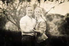 Composite image of grey background. Grey background against happy couple holding hands against trees Stock Images