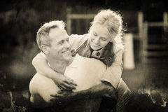 Composite image of grey background. Grey background against husband giving piggy back to wife Stock Image