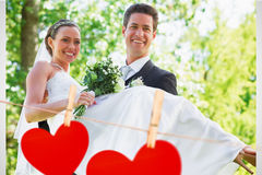 Composite image of groom carrying bride in garden Royalty Free Stock Photo